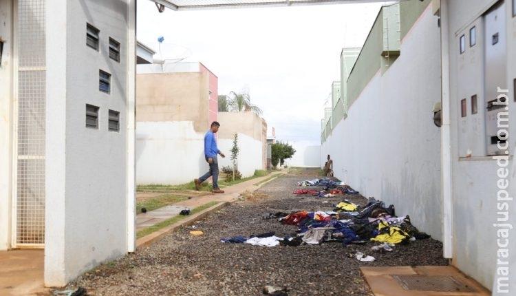 Após incêndio em vila de casas moradores tentam salvar roupas atingidas pelo fogo