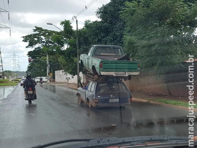 Condutor de carro transporta caminhonete no capô